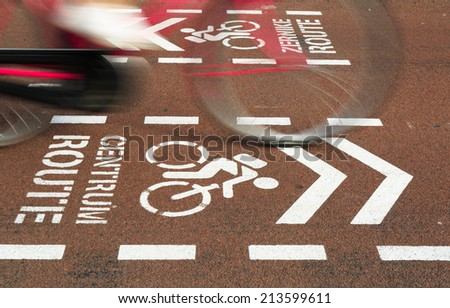Bicycle riding over a bicycle sign for the city center on a urban bicycle lane, motion blur of bicycle. - stock photo