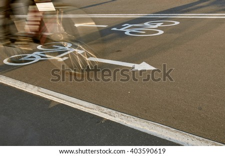 Bicycle road sign and bike rider in motion - stock photo