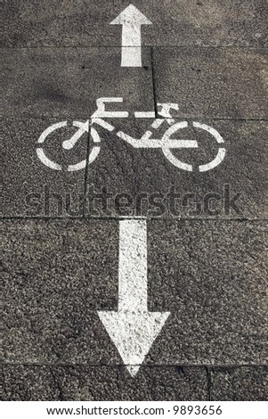Bicycle road sign painted on the pavement. - stock photo