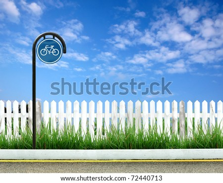 bicycle sign and white fence and blue sky - stock photo
