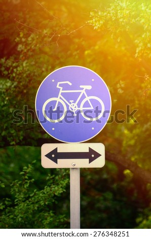 Bicycle sign in park with arrow in both directions