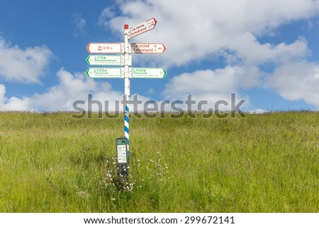 Bicycle signpost in Dutch countryside with direction indications to villages Urk, Lelystad, Schokland and Emmeloord and some interesting bicycle routes - stock photo