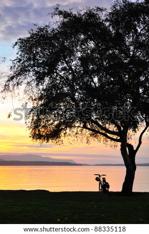 Bicycle silhouetted against setting sun - stock photo