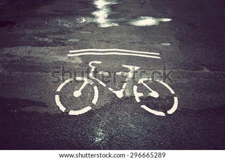 Bicycle symbol on city street. Bike sign on the road. Bike lane. Vintage effect. - stock photo