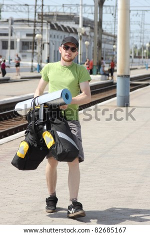 bicycle tourist with backpack walking and railroad station