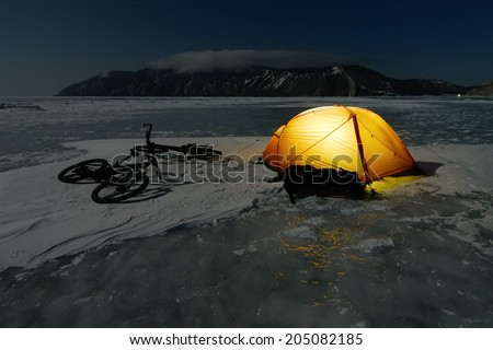 Bicycle tourists?? winter camp �¢?? orange tent and bikes on the surface of frozen lake. Night scene - stock photo