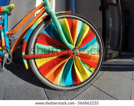 Bicycle wheel colorful knitted wool - stock photo