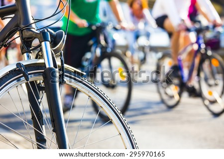 bicycle wheel detail with blurry cyclist - stock photo