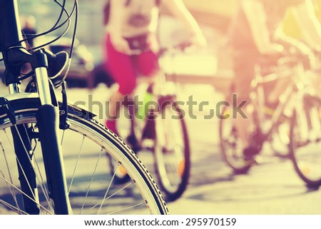 bicycle wheel detail with blurry cyclist with retro color effect - stock photo