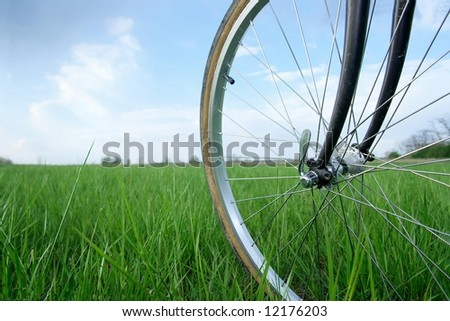 Bicycle wheel on a green field - stock photo