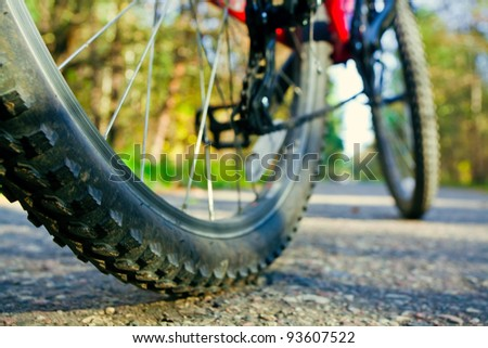 Bicycle wheel on road - stock photo