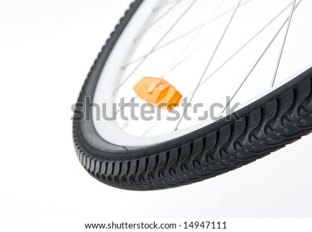 Bicycle wheel with orange reflector, shallow DOF. - stock photo
