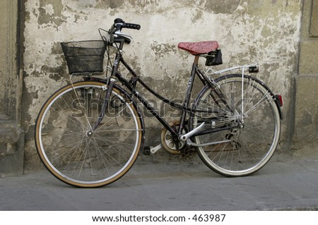 Bicycle with a red and black painted seat leaning against a wall - stock photo