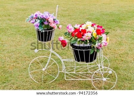 bicycle with artificial flower on grass - home exterior - stock photo