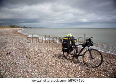 Bicycle with bags, stand on coast line. - stock photo