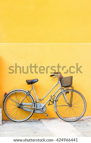Bicycle with basket and yellow wall. - stock photo