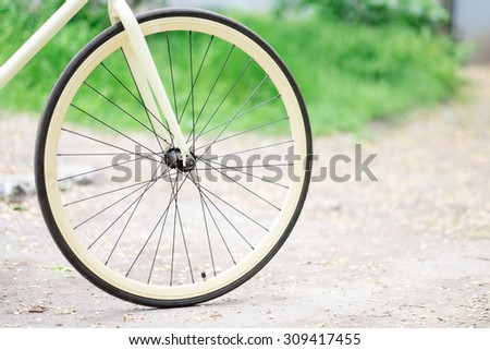bicycle yellow wheel on a background of grass - stock photo