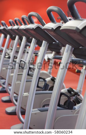 Bicycles in a row in a gym with red background and floor - stock photo