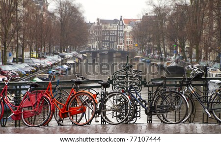 bicycles in amsterdam safe to the rail of the bridge - stock photo