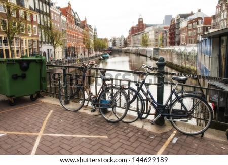 Bicycles lining a bridge over the canals of Amsterdam, Netherlands. - stock photo