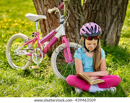 Bicycling girl. Girl rides bicycle. Girl in bicycling helmet read book on rest near bicycle. Bicyclist looking at book. - stock photo
