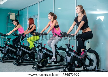 Bicycling to health. Four girlfriends athletes go and pedaled on a stationary bike at the gym. - stock photo