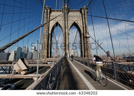 Bicyclist heading to Manhattan on the Brooklyn Bridge in morning light with blue sky and wispy clouds. - stock photo