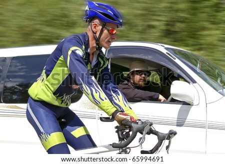 bicyclist overtakes a automobile - stock photo
