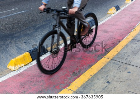 bicyclist red bike path in modern city - stock photo