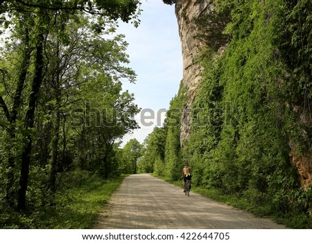 Bicyclist riding by the Missouri River bluffs - stock photo