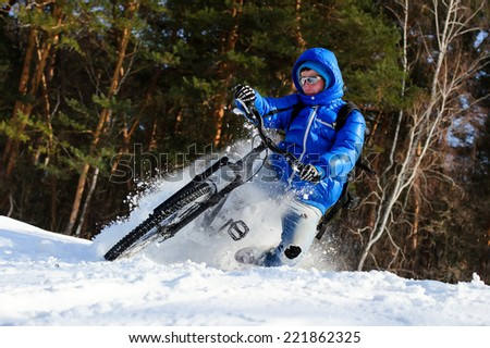 Bicyclist riding mountain bike in snow in winter forest - stock photo