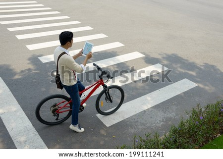 Bicyclist using his digital tablet as a navigator - stock photo