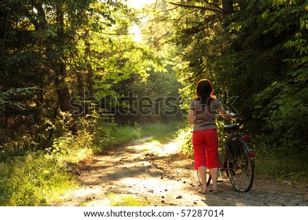 Bicyclist woman walk in the park with bikes - forest road - stock photo