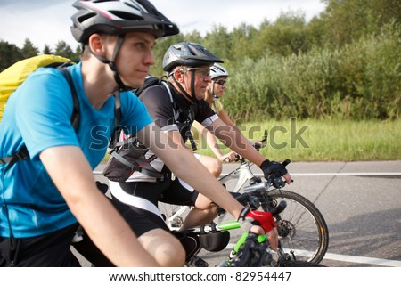 Bicyclists. Focused on middle cyclist. - stock photo