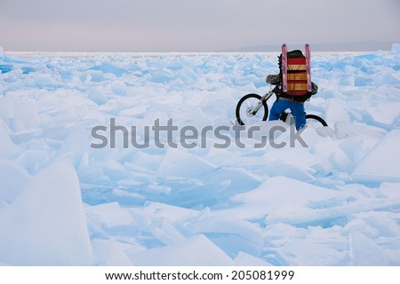 Bicyclists hardly walking through the field of cracked ice on the surface of frozen lake in the evening  - stock photo