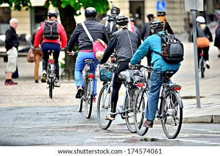 Bicyclists on their way home in the rain, properly dressed with helmets and gear - stock photo
