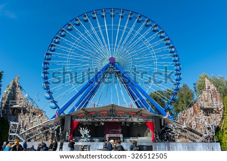 Biddinghuizen, Flevoland/Netherlands - October 11-10-2015 - Big ferris wheel with stage in front with a Halloween fright night theme at attraction park Walibi. People walking by.