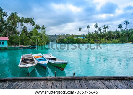 BIDUK BIDUK, INDONESIA - FEB 11: Boat at the Labuan Cermin Jetty on Feb 11, 2016. The lake is unique lake since it contains both fresh on the lake's surface while underneath is the salt water. - stock photo