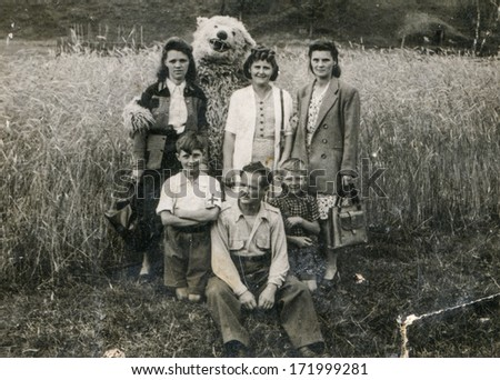 BIELSKO, POLAND, CIRCA 1940s - vintage photo of happy family with a fake bear outdoor