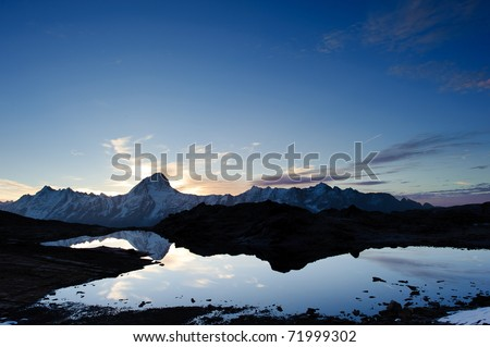 Bietschorn mountain peak at sunrise reflecting in small lake, Loetschenpass, Wallis, Switzerland - stock photo