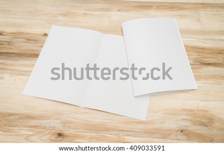 Bifold white template paper on wood texture - stock photo
