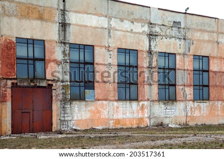 Big abandoned old factory building with doors and windows closed . Dirty wall with cracked plaster leafless - stock photo