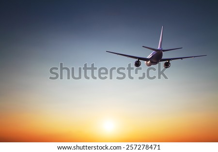 big airplane in the sky on sunrise - stock photo