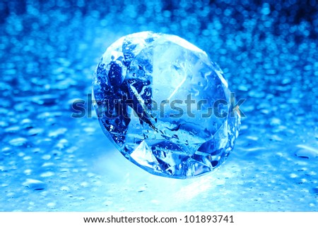 Big and beautiful jewel with water drops in blue light - stock photo