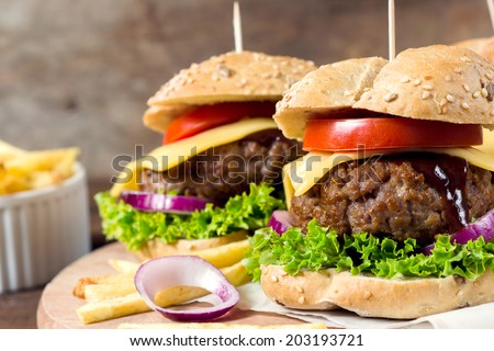 Big and juicy beef meat with cheese and vegetables in the ban.Selective focus on the front beef meat  - stock photo