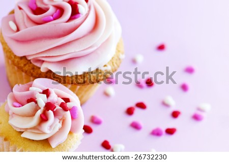 Big and small cupcakes with icing and sprinkles - stock photo