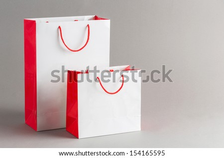 Big and small paper shopping bag isolated on gray background - stock photo