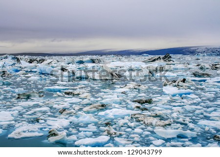 Big and small parts of icebergs floating in Iceberg lake in Iceland - stock photo