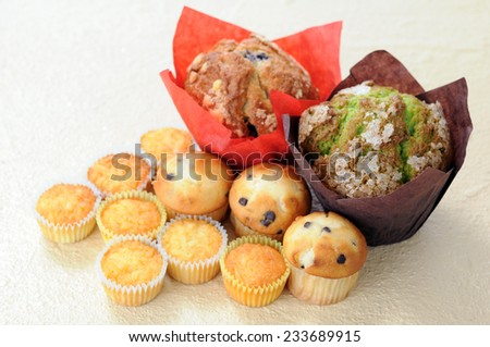 big and some mini muffins on table  - stock photo