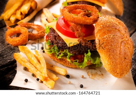 Big and tasty cheeseburger with onion rings and french fries.Selective focus on the cheeseburger - stock photo